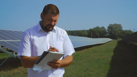 enviroment : Man holding records of solar panels and shows thumb up Stock Footage