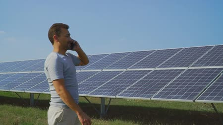 enviroment : Young man talking on the phone on the field with solar panels