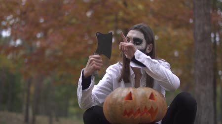questão : Halloween. Girl with a scary Halloween make-up is sitting with a butchers knife