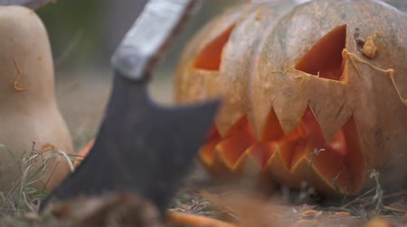 hallows : Halloween. Scary pumpkin and butcher knife in the forest. Halloween concept Stock Footage