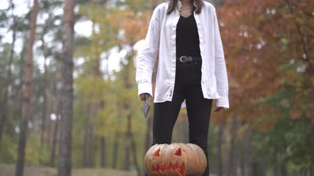 hallows : Halloween. Girl with a knife coming to Halloween pumpkin Stock Footage