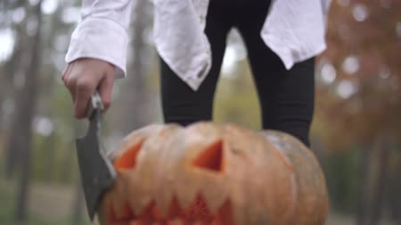 обряд : Halloween. Girl spends a knife on a Halloween pumpkin.