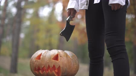 rito : Halloween. A girl with a knife is standing over a Halloween pumpkin.