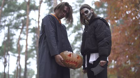 kult : Halloween. The guy and the girl with Halloween makeup in the forest.
