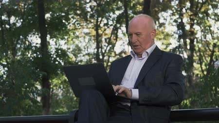нетбук : Mature man is working on netbook at the park Стоковые видеозаписи