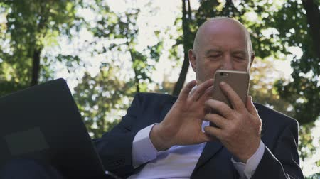 netbook : An old man is looking at a smartphone while sitting on a bench in the park