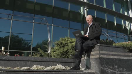interessado : Old man is working with laptop in the city Vídeos