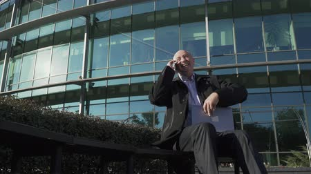 ilginç : Adult man talking on the phone near the business center Stok Video