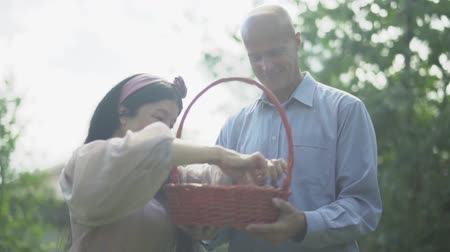 imitates : Mature couple with a basket of plums in the garden