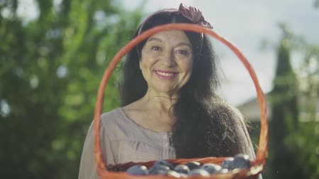 imitates : Mature woman holding a basket with plums