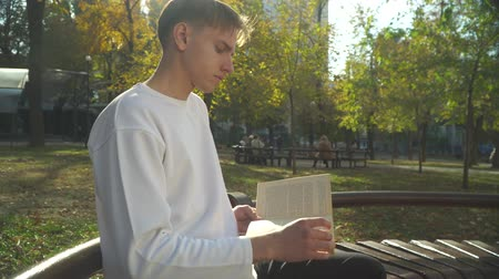 novel : Young man is reading book it the park