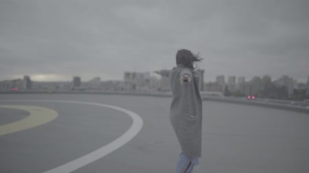 só : Lovely girl with arms outstretched walks in windy weather. Slow motion, s-log. Stock Footage