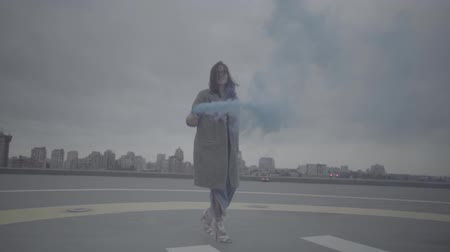 maiden : Cute woman with smoke bomb over city background. Slow motion, s-log, ungraded