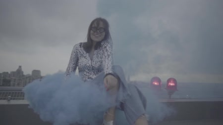 szobalány : Pretty woman with smoke bomb over city background. Slow motion, s-log, ungraded