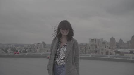 szobalány : Beautiful smiling girl on the background of the city. Slow motion, s-log, ungraded Stock mozgókép
