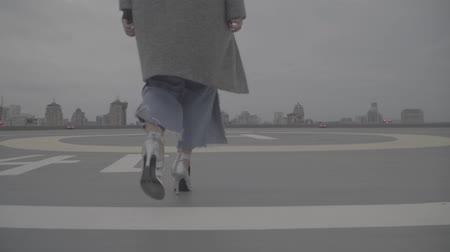 maiden : Woman in silver shoes goes against the background of urban buildings. S-log
