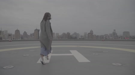 s : Cute girl goes on the background of the city view. Slow motion, s-log, ungraded Stockvideo