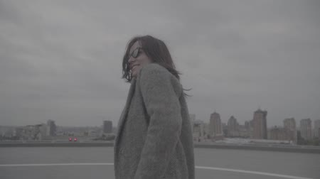 servant : Nice woman goes on the background of the city view. Slow motion, s-log, ungraded