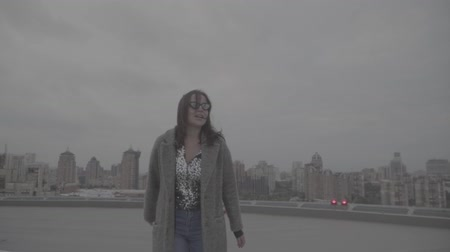 maiden : Brunette goes on the background of the city view. Slow motion, s-log, ungraded