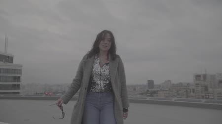 maiden : Cute girl goes on the background of the city view. Slow motion, s-log, ungraded Stock Footage