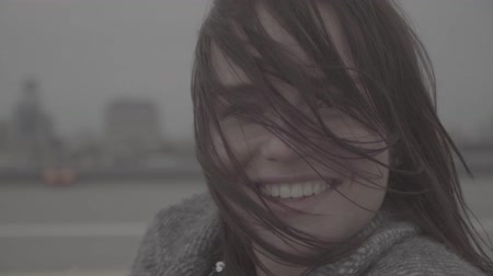 kül : Beautiful smiling girl on the view of city on background. Slow motion, s-log