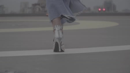 maiden : Legs of a girl in heeled sandals walks on the view of city on background. S-log
