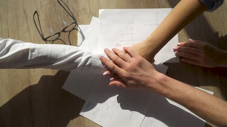 документация : Close-up of the hands of office staff folding each other