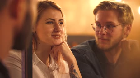karczma : Two girls and a guy laugh talking in a cafe at a table Wideo