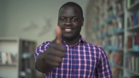 raises : African american man raises his thumb up in library Stock Footage