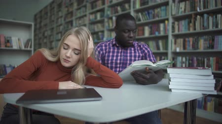 難しさ : African american man and european woman fall asleep in the library