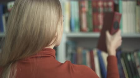 choise : The female is choosing which book to take in the library