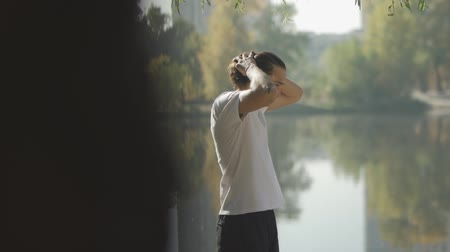 stay active : Tall male straightens his hair back at the lake Stock Footage