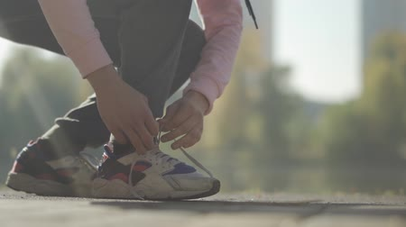 часть тела : Human hands tying shoelaces on sneakers Стоковые видеозаписи