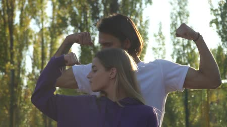 body building : Male and female demonstrate their muscles in the park Stock Footage