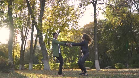 ırklararası : African American and Caucasian girl holding hands and spinning in the park Stok Video