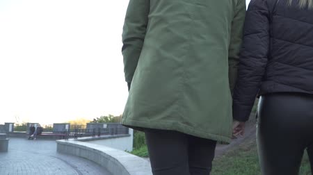 межрасовый : Young couple holding hands and walking outdoors. Slow motion