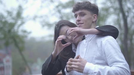 girfriend : Beautiful couple make a heart with their hands outdoors Young couple spends time together Couple in love Happy couple Stock Footage