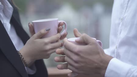 латте : Male and female hands hold cups of coffe in their hands outdoors closeup Male and female hands holding cups Close-up of male and female hands with cups Стоковые видеозаписи