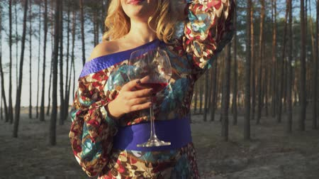 sahte : Beautiful woman standing in the forest with wine glass Lady with false eyelashes smiles Girl in summer dress with bare shoulder drinks wine outdoors Blonde with green eyes and long eyelashes