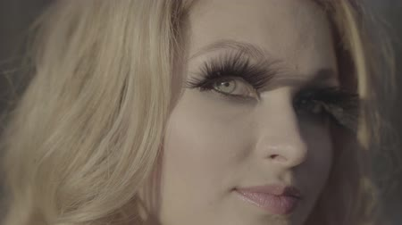 sahte : Portrait of adult lady has fake eyelashes Pretty woman looks on the camera Face of a girl close up Blonde with green eyes and long eyelashes. S-log, ungraded Stok Video