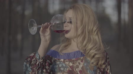 sahte : Portrait of blonde woman drinking wine in the forest Lady with false eyelashes rest outdoors Girl in summer dress with bare shoulder drinks wine outdoors Blonde with green eyes and long eyelashes S-log, ungraded Stok Video