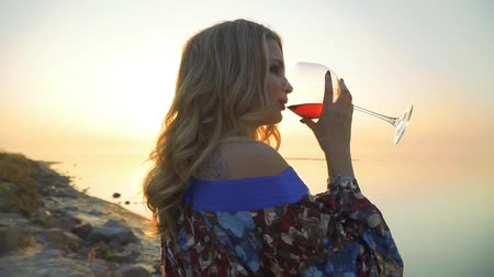 custo : Portrait of blond female drinking wine at the seaside close up Lady enjoys landscape alone Girl in summer dress with bare shoulder drinks wine outdoors Sun in a glass of wine