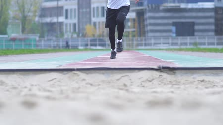 chmiel : Young guy in sportswear accelerates and jumps in the sand in front of the camera Sand scatters from under the feet of a jumper who jumped in front of the camera Healthy lifestyle