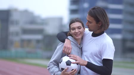 apertado : Portrait of a beautiful young couple in sportswear outdoors Handsome guy in sportswear kisses his girlfriend on the cheek Sports couple in love embracing and holding a ball Healthy lifestyle