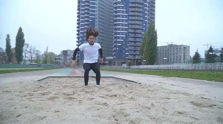 stadion : Handsome guy in sportswear accelerates and jumps in the sand in front of the camera Sand scatters from under the feet of a jumper who jumped in front of the camera The camera moves from right to left Healthy lifestyle