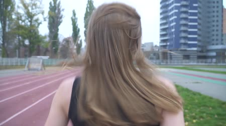 velocímetro : The camera moves behind the girl running outdoors A girl with long hair and a sports t-shirt runs in a sports stadium Back view Healthy lifestyle Stock Footage