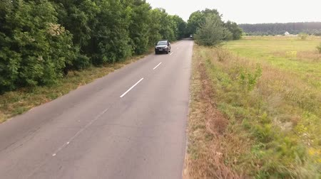 germany : Big black car is riding countryside road People are travelling by car Shooting from the drone
