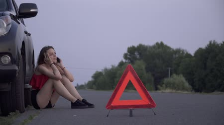 caution sign : Upset girl near her wrecked car Young woman is sitting near broken car Woman is sad Female is calling by mobile phone Car trouble Stock Footage