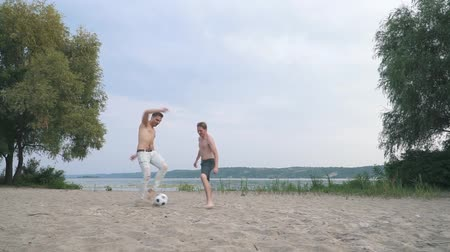 kabarık : Two young guys playing football Competition between people Friends have a fun together Spending time outdoors Active lifestyle Stok Video