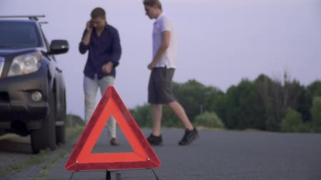 придорожный : Two guys next to a broken car standing on the side of the road. One guy calls for help on the phone and the second is watching the wheel Car trouble Focus on the foreground